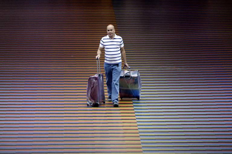 Homem carrega duas malas ao passar pelo carpete degradê, de cores lilás, laranja, amarelo, verde, azul, violeta