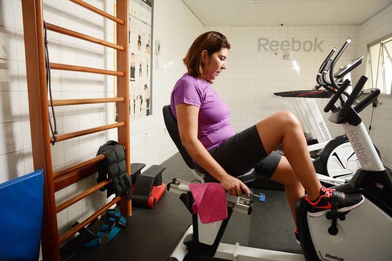 Paula Helena Lima pedala em uma bicicleta ergométrica em uma sala de ginástica com pesos espalhados pelo local, além de outros equipamentos