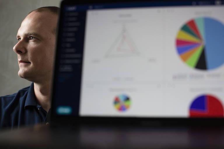 O empresário Leonardo Militelli, sócio da Ibliss Digital Security, posa atrás de um computador cuja tela mostra dados sobre segurança