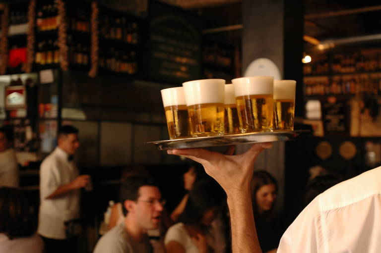 Garçom circula com copos de chope no salão do bar Filial, na Vila Madalena