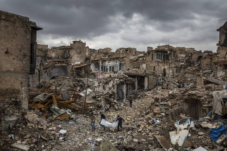 homens carregam corpo em meio a cidade destruída