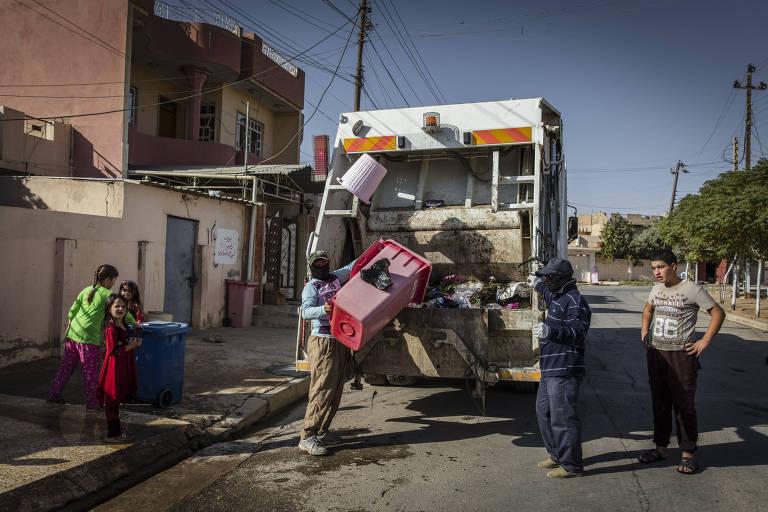 Homens fazem coleta de lixo