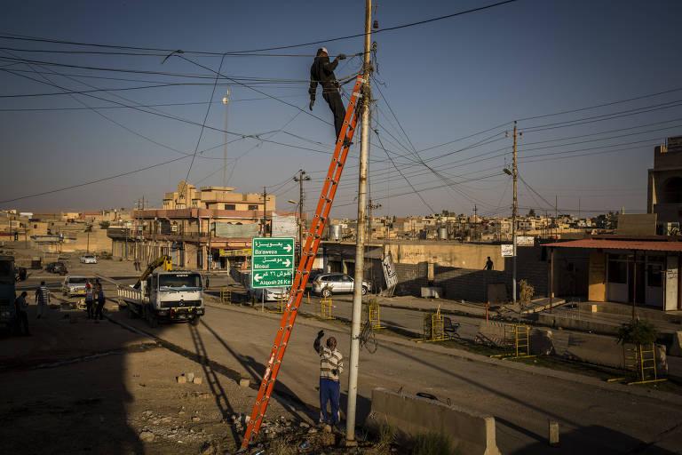 Homens trabalham em poste de eletriciadade