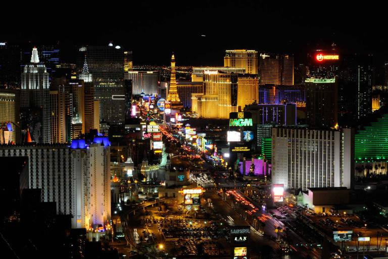 Vista aérea da via Las Vegas Strip, a rua mais movimentada de Las Vegas. A imagem, feita à noite, mostra os prédios de hotéis e cassinos iluminados, enquanto carros trafegam pelas ruas