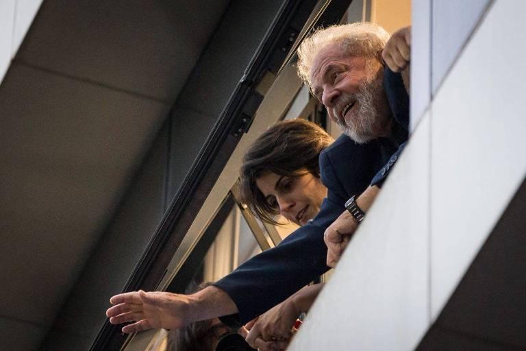 O ex-presidente Lula, ao lado de Manuela Dávila, acena para militantes da janela do Sindicato dos Metalúrgicos do ABC, em São Bernardo do Campo