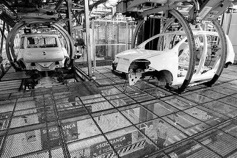 Carcaças de carros suspensas por garras em fábrica de automóveis