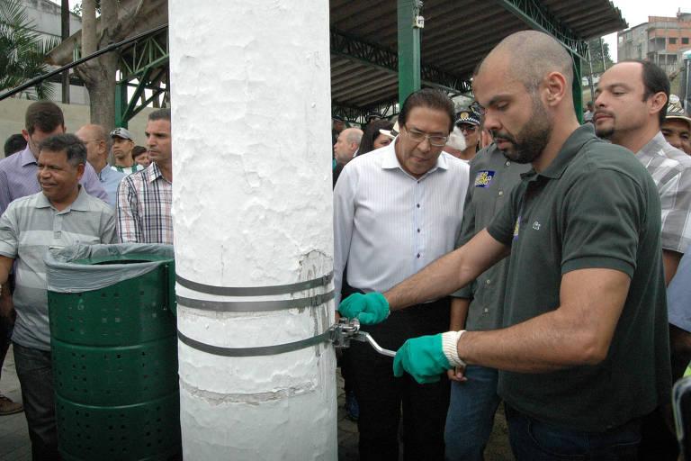 Com luvas verdes de borracha, Bruno Covas faz manutenção em um poste de luz