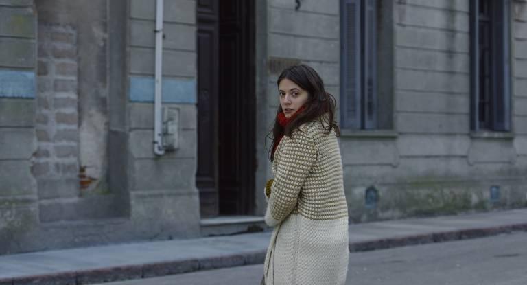 Foto mostra uma moça numa rua deserta; ao fundo veem-se prédios antigos, ela está de costas e seu rosto virado para a câmera, como se tivesse se voltado ao ouvir seu nome, surpreendida