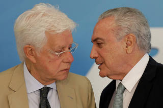 Brazil's President Michel Temer speaks with Minister of the General Secretariat of the Presidency of Brazil Wellington Moreira Franco during a ceremony to sanction flexible broadcast schedule of the Voice of Brazil radio program, in Brasilia