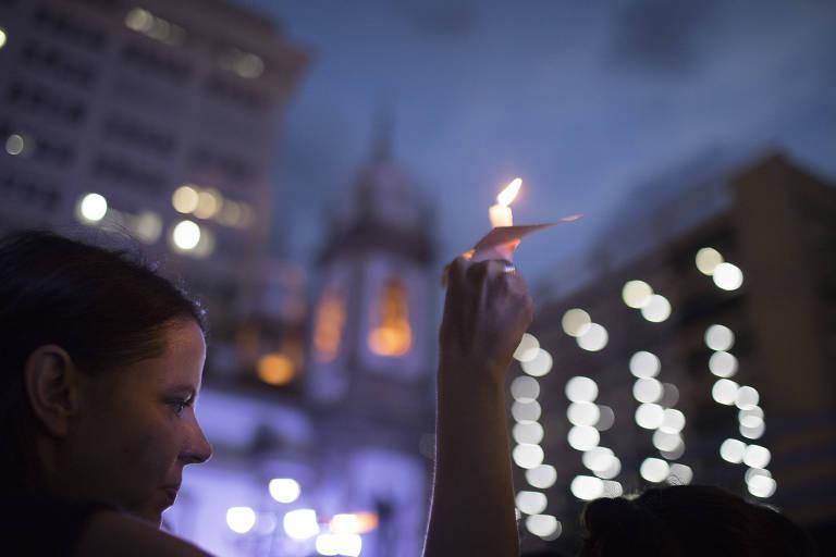 Mulher carrega vela em protesto contra a morte da vereadora Marielle Franco, assassinada no dia 14 de março, no Rio