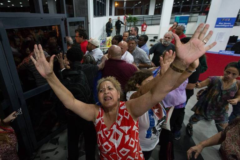 Apoiadores do ex-presidente Lula ameaçam repórteres na frente do sindicato dos metalúrgicos, em São Bernardo do Campo; na foto, mulher ergue os braços na tentativa de bloquear gravação de imagens
