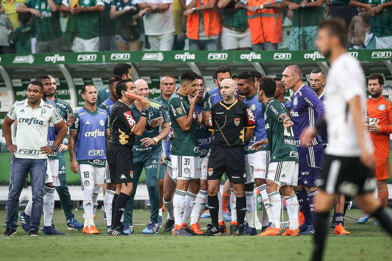 Jogadores do Palmeiras pressionam Adriano de Assis Miranda, quarto árbitro do clássico contra Corinthians, após anulação de pênalti