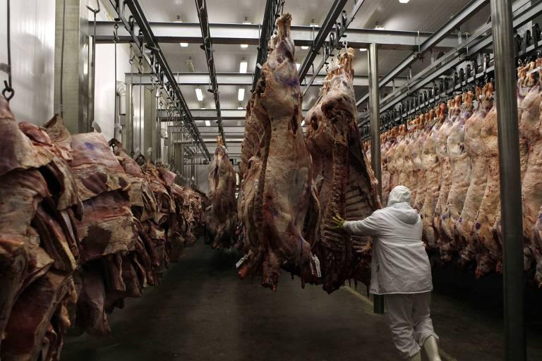 Trabalhador na linha de produção do frigorífico Marfrig, com dezenas de peças de carne penduradas