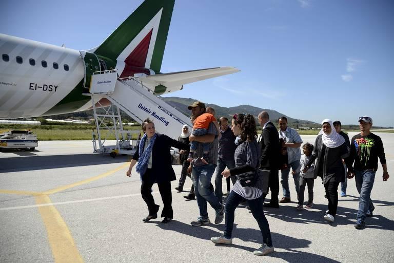 Um grupo de refugiados sírios embarca em avião com o papa Francisco no aeroporto de Lesbos; família foi levada ao Vaticano