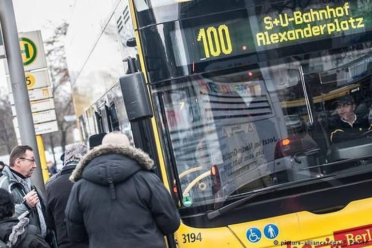 Passageiros esperam ao lado de ponto na rua para embarcar em um ônibus. O letreiro indica que é a linha 100, que vai até Alexanderplatz, em Berlim