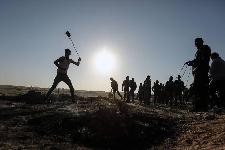 Palestinos atiram pedras contra forças israelenses em confronto na faixa de Gaza, em 31 de março