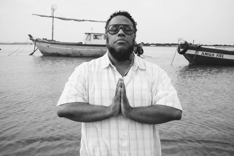 O músico carioca BNegão junta as mãos em um sinal de prece; ele veste uma camisa branca de manga curta e óculos escuro; atrás dele está o mar, com dois barcos de pescador