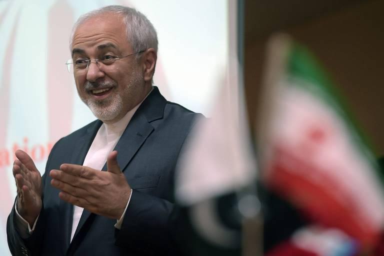 Mohammad Javad Zarif aparece de terno sem gravata, sorri e gesticula com as mãos enquanto fala em um evento; à frente da foto, uma bandeira do Irã ao lado de uma bandeira paquistanesa, ambas em imagem desfocada