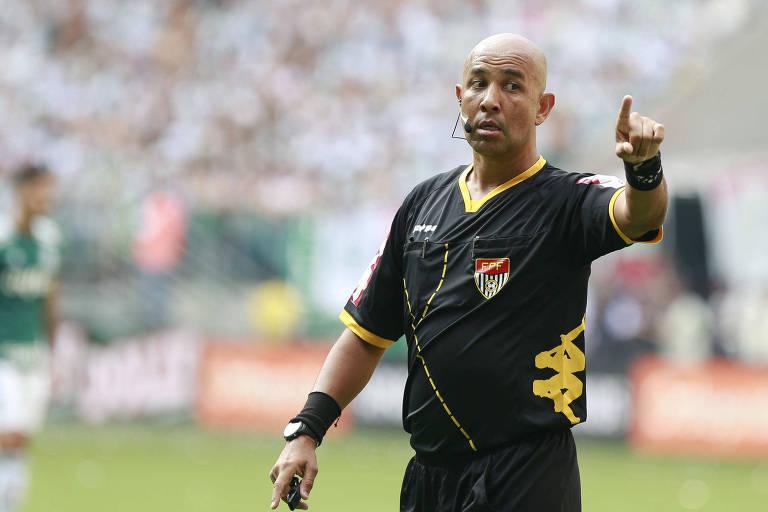 O árbitro do decisão entre Palmeiras e Corinthians com o braço esquerdo esticado
