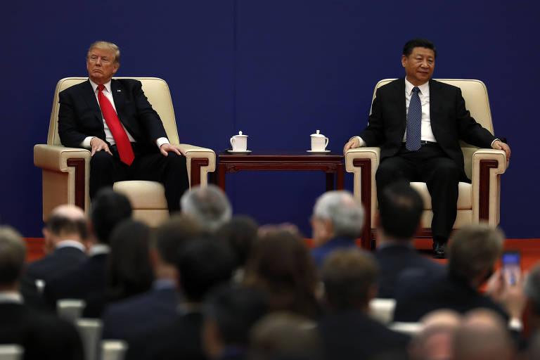 Os presidentes Donald Trump, à esq., dos EUA, e Xi Jinping, da China, durante evento em Beijing