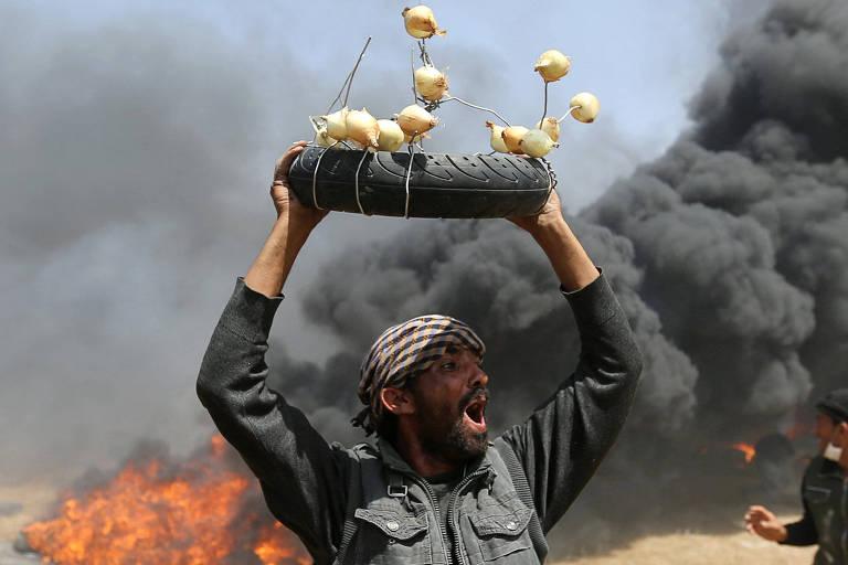 Manifestante palestino ergue pneu com cebolas durante confronto com tropas israelenses na fronteira de Gaza