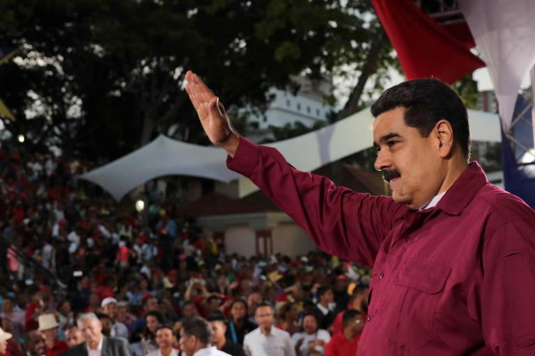 De perfil à direita, Maduro, que veste camisa vinho, levanta o braço esquerdo para acenar a seus seguidores, que aparecem ao fundo