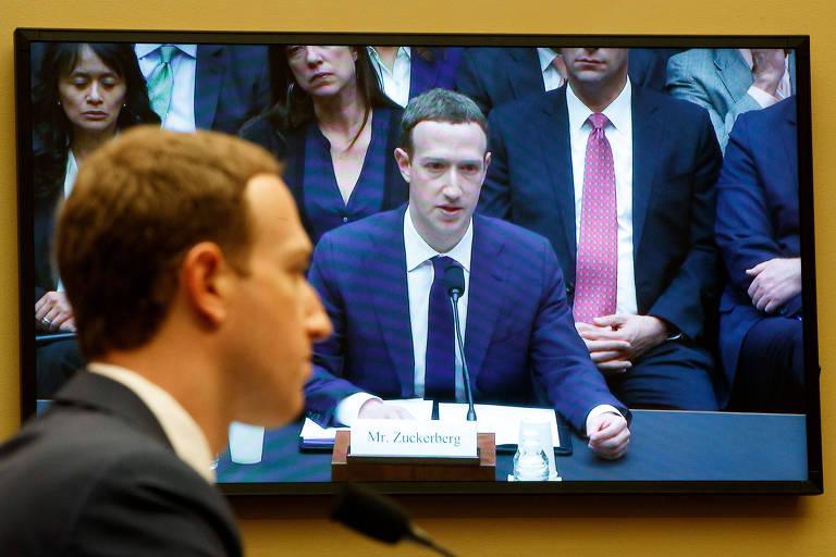 Zuckerberg aparece de perfil à esquerda, frente a um microfone da sessão; atrás, televisão reproduz a mesma imagem, mas com uma câmera de frente