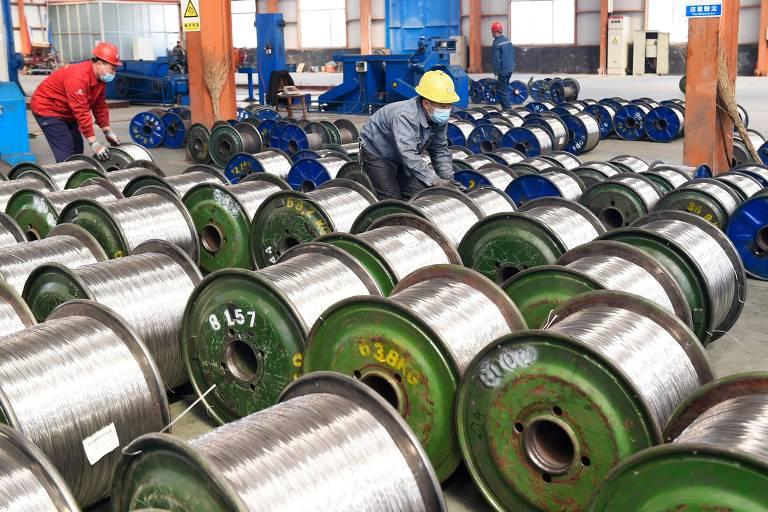 Trabalhadores movem bobinas de alumínio em fabrica na província chinesa de Shandong
