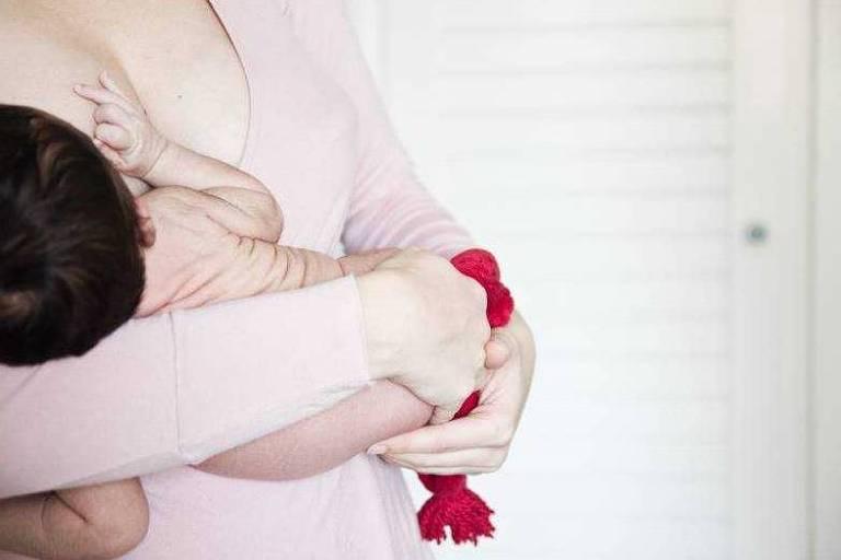 Bebê dorme no colo da mãe após ser amamentado