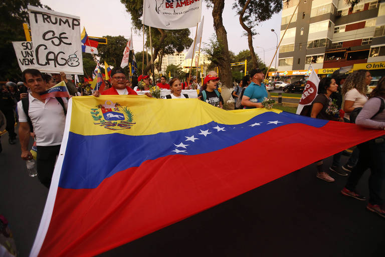 Grupo carrega uma bandeira venezuelana e cartazes de organizações sociais, em sua maioria brancos, em uma rua