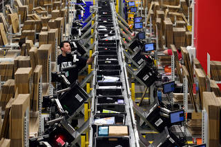 Workers process purchased orders at a packaging area inside Amazon distribution center in El Prat de Llobregat, near Barcelona