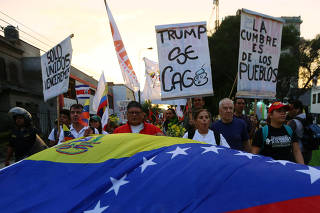 People holding a Venezuelan flag march prior to the Summit of the Americas in Lima