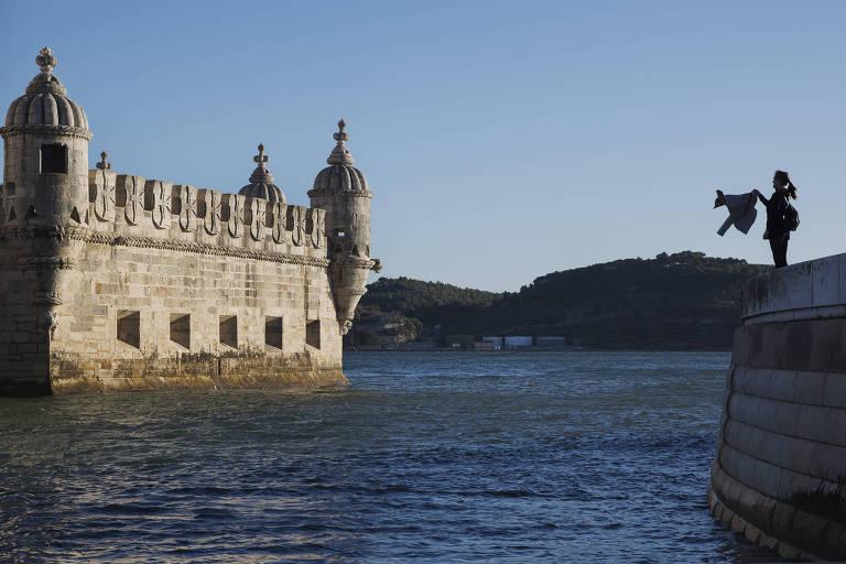 Turista tira foto da Torre de Belém, às margens do rio Tejo, na capital Lisboa