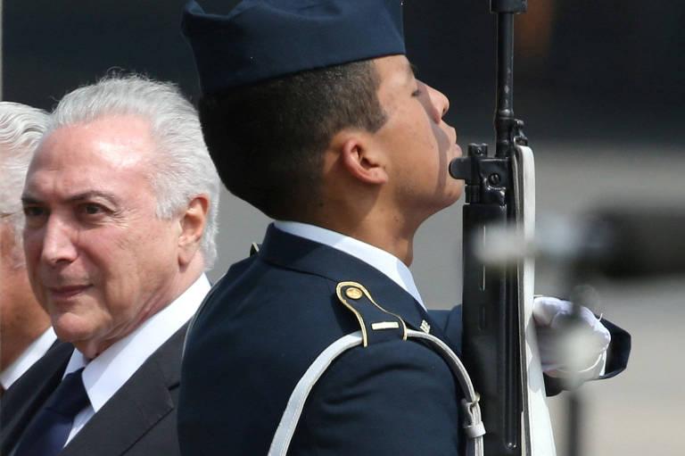 Temer passa com feição séria à esquerda de um soldado peruano armado com fuzil; vestido de farda azul marinho, quepe e luvas, o militar aponta a arma para cima; os dois aparecem na imagem do torso para cima