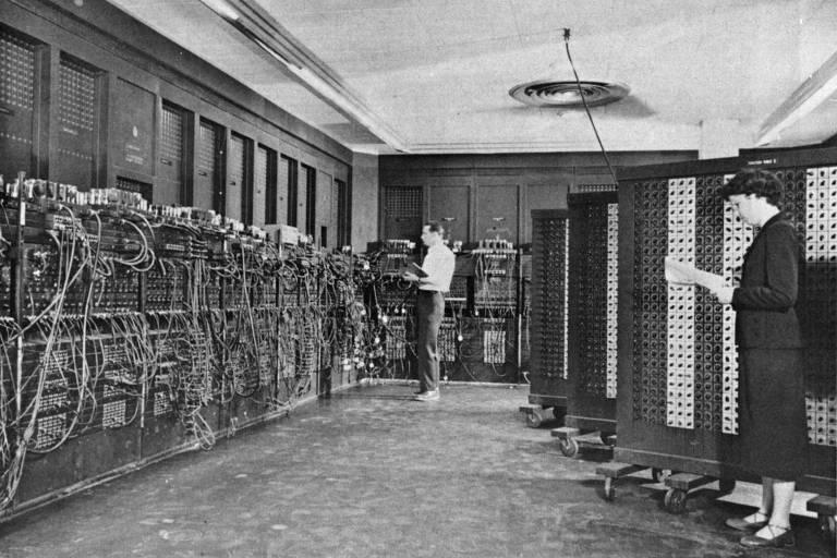 Em meio a fios, em uma grande sala, duas pessoas trabalham. Os amontoados de fios conectados lembram os que eram usados em centrais telefônicas antigas