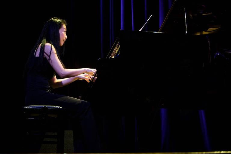 A pianista Makiko Yoneda está sentada tocando piano