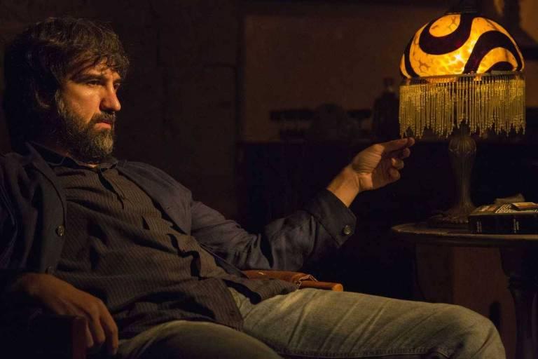 O ator Charles Fricks está sentado em uma poltrona ao lado de um abajur ligado