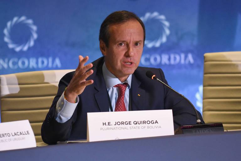 """De terno azul marinho e gravata vermelha, Jorge Quiroga aparece falando e gesticula com a mão direita; à sua frente sai uma placa com seu nome e a inscrição """"Estado Plurinacional da Bolívia"""" em inglês; atrás, painel azul com o símbolo da Concordia, organização não governamental"""