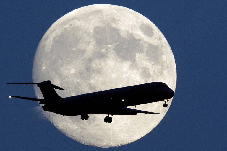 Avião sobrevoa em frente a lua