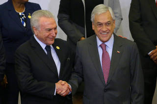 Brazil's President Michel Temer and Chile's President Sebastian Pinera shake hands at the family photo during the VIII Summit of the Americas in Lima