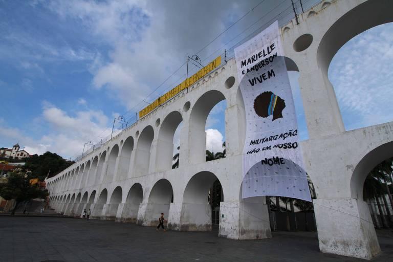 """Bandeira colocada nos Arcos da Lapa, no Rio de Janeiro, em homenagem a Marielle Franco e Anderson Gomes. Bandeira tem os dizeres """"Marielle e Anderson vivem. Militarização: não em nosso nome"""""""