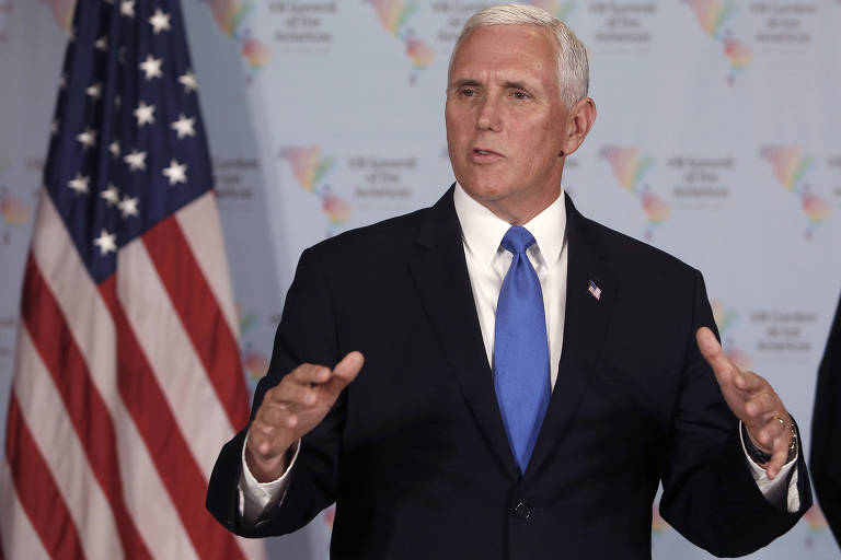 De terno preto e gravata azul clara, Pence fala e gesticula com as mãos abertas; atrás dele à esquerda aparece uma bandeira dos Estados Unidos; imagem é cortada pouco abaixo do peito de Pence