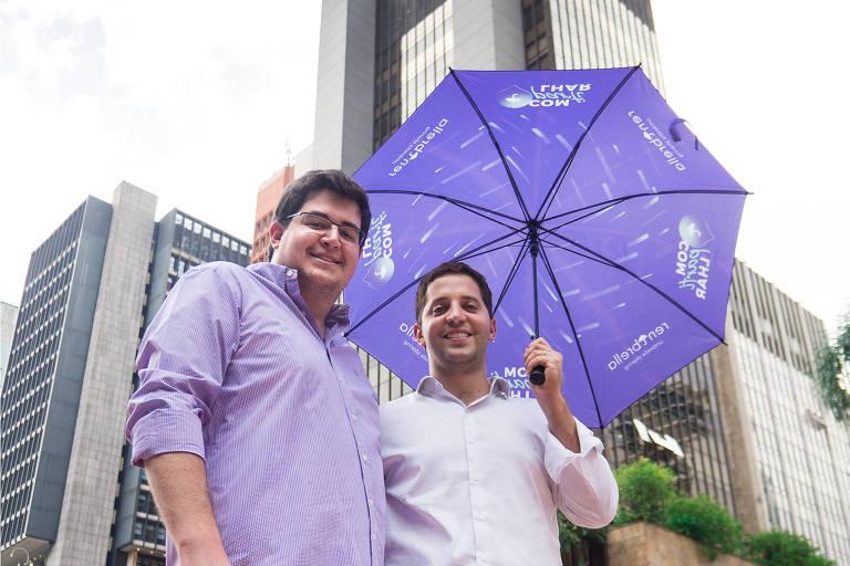 Os empresários Nathan Janovich (esq.) e Freddy Marcos, criadores da Rentbrella, que aluga guarda-chuvas, em avenida em São Paulo, segurando um guarda-chuva roxo da marca
