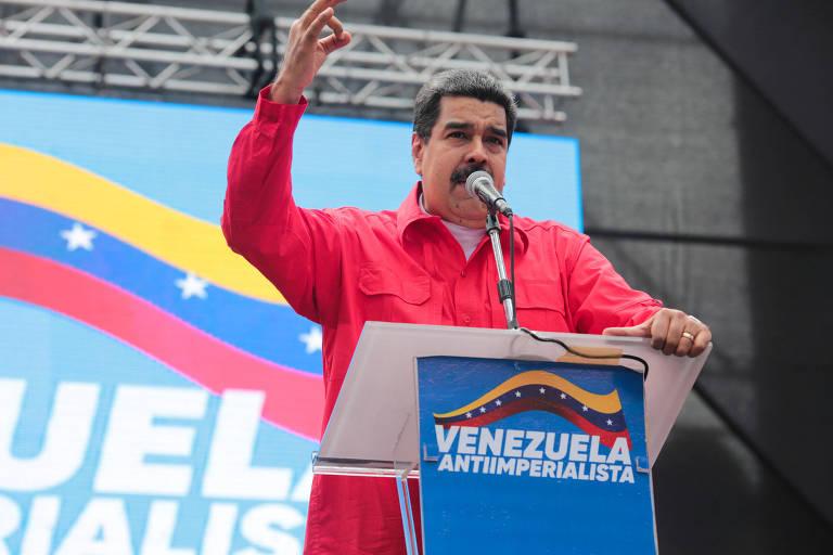 De camisa vermelha e com o braço esquerdo em riste, Maduro fala no microfone em um púlpito azul enfeitado com a bandeira da Venezuela estilizada com a inscrição Venezuela antiimperialista; ao fundo, o telão mostra a mesma arte estilizada