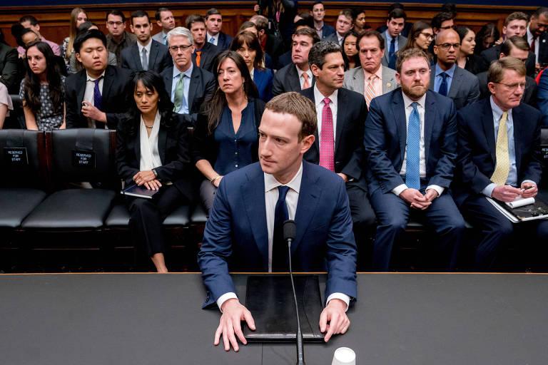 Zuckerberg aparece de terno azul marinho e gravata preta, apoiando as mãos sobre um tablet que está sobre uma mesa preta; atrás, cerca de 20 pessoas assistem à audiência