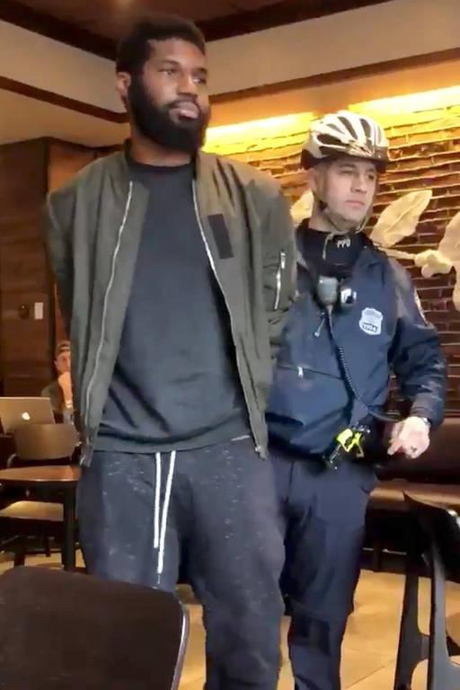Homem negro com mãos amarradas às suas costas caminha com polícial fardado logo atrás dele.