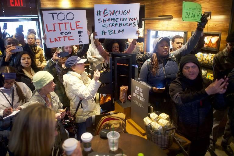 Manifestantes com cartazes dentro de uma cafeteria