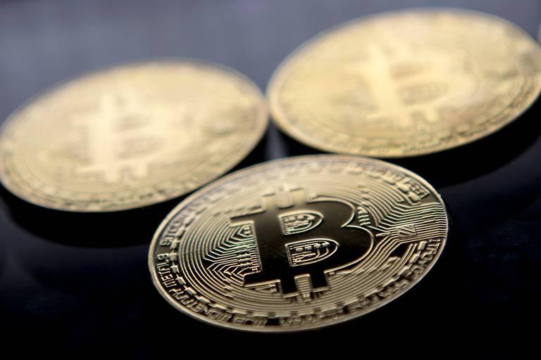 Três moedas folheadas a ouro com o símbolo da criptomoeda bitcoin