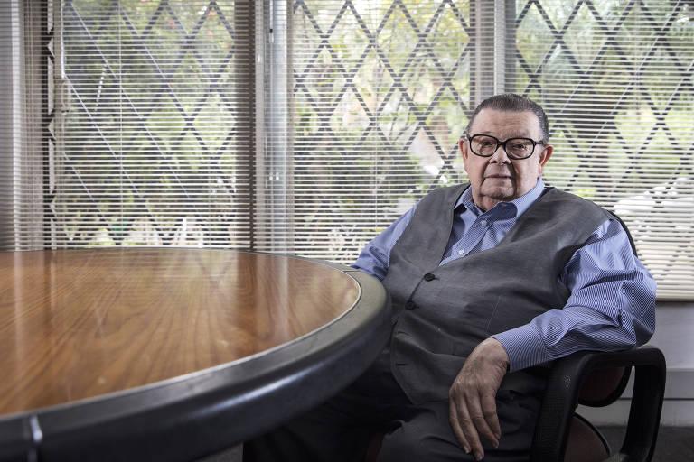 O ex-ministro e economista Delfim Netto, vestindo camisa azul e colete cinza, na sala do seu escritório, no Pacaembu, em São Paulo.