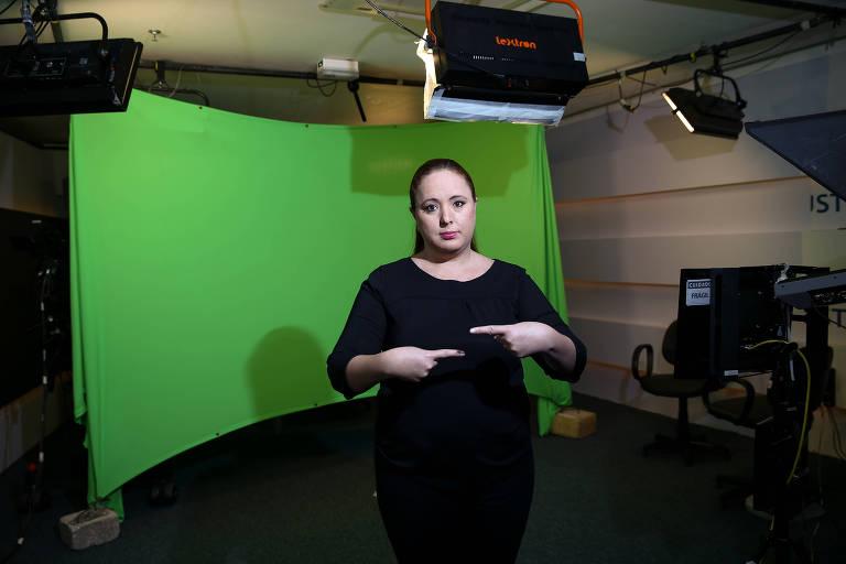 Dânnia Esteves Oliveira, intérprete de libras do STF, no estúdio da TV justiça, onde são feitas as transmissões. Ela aponta os dedos indicadores um para o outro. Ela está de roupa preta em fente a um fundo verde. Há holofotes no estúdio.